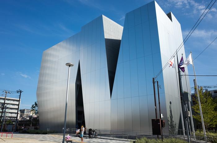 都営地下鉄大江戸線の両国駅より徒歩5分の所にあるのが「すみだ北斎美術館」です。葛飾北斎が墨田区で生涯のほとんどを過ごしたことから、この場所に作られたそうです。スリットの入った、淡い鏡面のアルミパネルで覆われた外壁には、墨田の風景がやさしく映り込みます。この美術館を設計したのは日本を代表する建築家の1人である妹島和世氏です。