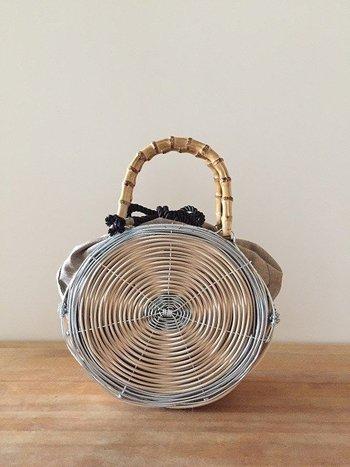 アルミワイヤーを使った雑貨やバッグを作るコリフェさん。しなやかに形を変えるアルミワイヤーの変幻自在さにも驚くけれど、異素材を大胆に組み合わせるなど、かなり高度な感性とテクニックで魅力的な作品を数々生み出しています。こちらのオーバル型のかごバッグは、籐とアルミワイヤーのコラボが絶妙。籐のかごバッグよりもスタイリッシュでかっこよく、けれど柔らかい雰囲気も醸し出しています。