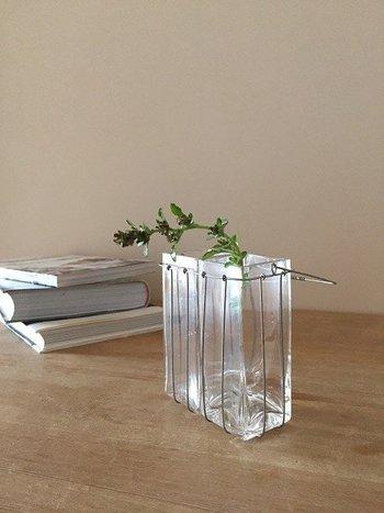 直方体のガラスの花瓶を2つ仲良く並べてアルミワイヤーのかごに収めた作品。アルミワイヤーに包まれることで、ガラスに柔らかさがプラスされるのが不思議。シンプルだけどとても表情豊かなフラワーベース。ただそこにあるだけの存在感にも魅了されます。