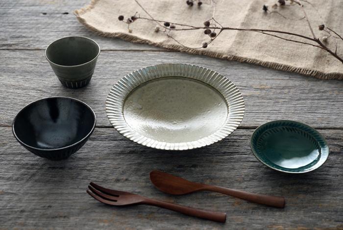 グレーや深緑、トルコブルーなど、大人っぽいアースカラーと丹波伝統のしのぎ模様が印象的な市野耕さんの器。伝統を大切にしつつ、自然色を求め自分で調合した釉薬を使うなど実験的な手法にも積極的。しっかりとぶれない作家の姿勢や温度感が伝わる作品です。