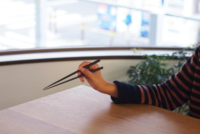 お箸の持ち方をおさらいしましょう。練習をする時は、下のお箸を安定させることです。  ①まず写真を撮る時にする様な「ピース」の形を指で作ります。 ②親指を立てて力を抜き、人差し指と親指の間に下のお箸を乗せます。 ③その時に、薬指の爪の生え際部分に、下のお箸が当たるようにしてください。※上の画像を参照 ④ピースをした2本の指と親指で上のお箸を持ちます。 ⑤上のお箸を3本の指で上下に動かした時、下のお箸を支えている指には力をいれないようにします。