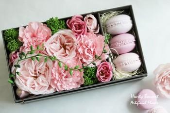 プリザーブドと同様、人気なのがアーティフィシャルフラワー。高品質な造花のことで、その美しいつくりがポイント。こちらのボックスは、バラの香りをつけた石膏のマカロンとセット。