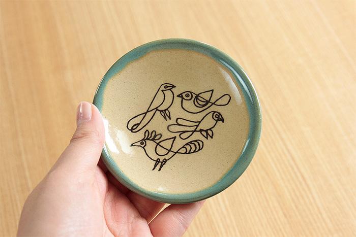スウェーデンを代表する世界的な陶芸アーティスト、リサ・ラーソン氏が手がけた豆皿は、日本好きの彼女が100回目の益子の陶器市の記念として「ひゃっかいめのとり」を描いた3寸 9cmの益子焼きの豆皿です。