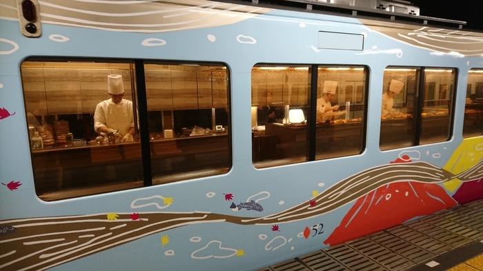 西武鉄道沿線の代表的な観光地である秩父の四季を荒川の水とともにイメージした車両デザインで、4両編成の列車は1号車から順に、春の桜、夏の山の緑、秋の紅葉、冬の氷柱をイメージした外装になっています。こちらの写真は3号車、秋の外装のキッチン車両です。窓越しにシェフの姿が見えますね。