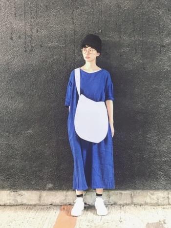 鮮やかブルーのゆったりワンピースに白のビッグショルダーを斜めがけ。バッグもコーディネートの一部として存在感を持たせることができますね。