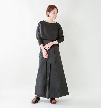 首元の開きが女性らしい黒のスウェットトップスに、同色のロングスカートを合わせた着こなし。一見するとワンピースのようにも見えるので、楽チンなのに上品なコーデが叶います。靴下の赤色を差し色に使っているのがポイントです。