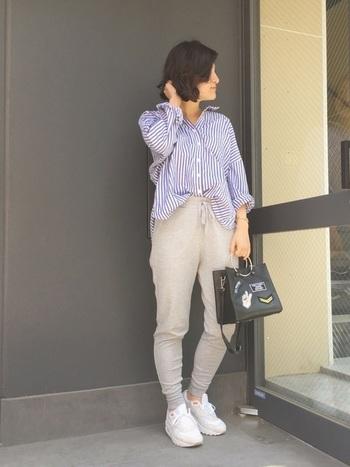 ラフなスウェットパンツに、あえてシャツを合わせたキレイめ×カジュアルミックスコーデ。足元はスニーカー、バッグはかっちりした印象のハンドバッグ。カジュアルさと上品さを程よくミックスさせ、大人のゆとりを感じさせる着こなしに仕上げています。