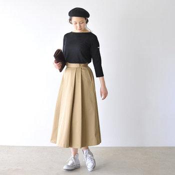 ハイウエストのベージュロングスカートに、黒のシンプルトップスをボトムスインしたスタイリング。ベレー帽や白スニーカーなどの小物でカジュアルさをプラスして、レディライクになり過ぎないような着こなしに仕上げています。