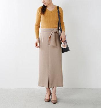 ベージュのタイトロングスカートに、マスタードカラーのニットを合わせた着こなし。ぼんやりとしやすいベージュのハイウエストボトムスには、はっきりした色を合わせるのがポイント。パンプスとスカートのカラーを合わせることで、脚長効果も期待できます。
