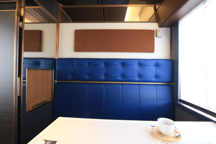 個室の中には、深い青がとても印象的なシートが。つい見とれてしまうほどの色です。外観の白、廊下の茶色、そしてこのシートの青。色彩だけでもとても美しく、感動を覚えます。そして、壁面は福島の刺子織をモチーフにした生地なのだそうです。