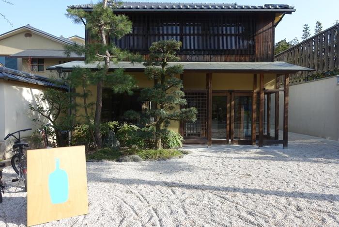世界中に熱狂的なファンがいるアメリカ生まれの「ブルーボトルコーヒー」が京都に初上陸!  築100年以上の京町屋をリノベーションした外観は風情溢れる佇まい。写真の建物が珈琲豆などが購入できるショップ、脇の玉砂利の小道を進むと、奥に本格ドリップコーヒーが味わえるカフェがあります。好みのコーヒーが見つかる「カッピングスペース」も。入口にあるブルーボトルのロゴが入った大きな看板が目印です。