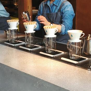 カフェではコーヒーを一杯ずつドリップするバリスタの姿が。  「ブルーボトルコーヒー」のコンセプト「焙煎したてのフレッシュな珈琲豆だけを使い、最も美味しいフレーバーで飲んでいただきたい」という思いが伝わるおもてなしです。  5年かけて開発したという有田焼の専用ドリッパーは、熱伝導の良さ、軽さ、薄さが備わっていて、冷めることなくお客さんに提供できるという特徴があるそう。