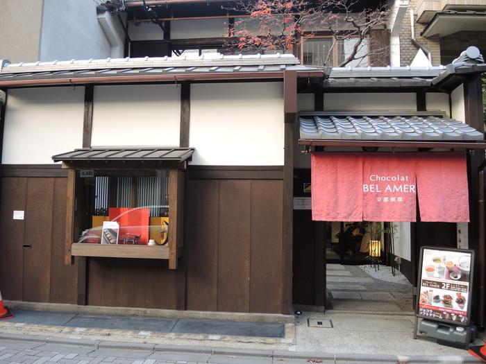 「ベルアメール」は、美しい装飾を施したパレットチョコレートなどで日本のチョコレート界に衝撃を与えた東京で人気のショコラトリー。「京都別邸」は唯一のカフェ併設店です。町家にかかる赤い暖簾が目を引きます。