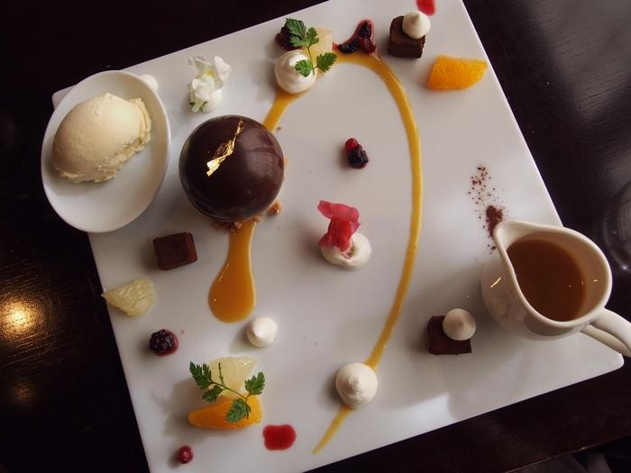 こちらは、カフェメニューのひとつ「ドーム オ ショコラ」。芸術的な一皿で目を奪われますね。  チョコレートドームの中には、丹波産コシヒカリを使用したバニラのリオレと柚子風味の柑橘ジュレが詰まっています。温かい柚ソースをかけ、溶けていく過程をも楽しめる一品。