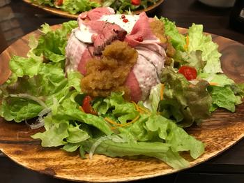 2種類のソースがかかったローストビーフサラダ丼は、ウッドプレートにダイナミックに盛り付けられています。柔らかなお肉とさっぱりしたソース、しゃきしゃき野菜がとまらないおいしさ。