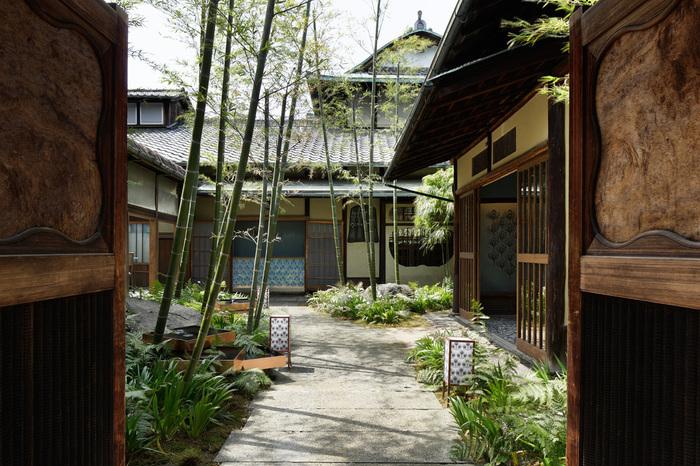 京都、宇治にある名茶舗「上林春松本」の茶葉を使ったお茶を急須で入れて楽しめるカフェ「Salon de KANBAYASHI 」。1925年に建てられた邸宅をリノベーションし、700坪のアカネリゾート敷地内にある蔵を改装した非日常が味わえる隠れ家的サロンです。 重厚な扉の奥には風情ある建物と美しい庭が広がっています。