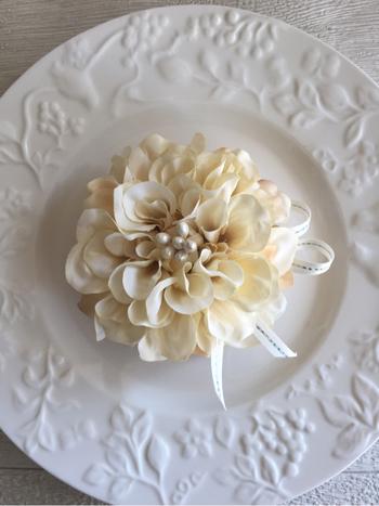 お母さんに、感謝を表す花をモチーフにしたアクセサリーを贈るのも素敵!たとえば、こんな白いダリアのコサージュはいかが?上品でエレガント、スカーフなどをとめるのもおしゃれです。コサージュは、自分で作ることもできますよ。