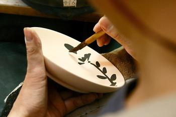 「染付(そめつけ)」とは、青色の顔料「呉須(ごす)」で絵付けをした焼きもののことです。このように筆を用いて描くことだけでなく、皿表面に図案を転写したり、呉須を吹きかけたり…。表現方法は様々です。 素焼きした素地に描き終えたら、この上に透明な釉薬をかけて本焼きします。すると呉須は、 藍色を帯びた、深みのある色味に変わります。