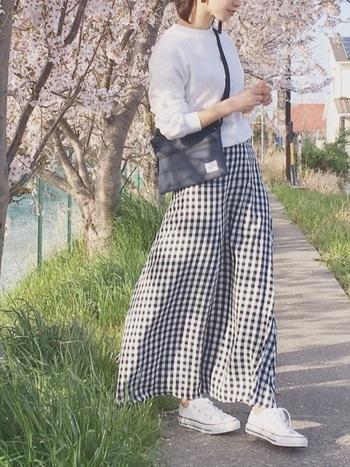 シンプルで春夏らしさ満点のコーデ。ギンガムチェックのロングスカートには、白スウェットに白スニーカーを合わせて爽やかに。