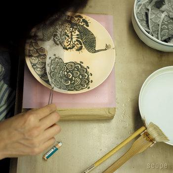 「印判(いんばん)」は、紙に描かれた絵柄(転写紙)を、陶器に刷りこんで転写するという、絵付けの技法です。絵皿の大量生産を可能にするものとして、明治以降に行われるようになりました。転写紙を使うとはいえ、刷りこむのは手作業。線の滲みやゆがみなど、独特の風合いがありますよ。 素焼きした素地に転写し終えたら、この上に釉薬をかけて本焼きします。