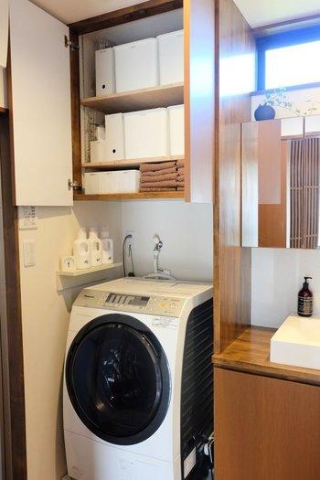 洗濯機上部の備え付けの棚には、白で統一した収納ボックスが整然と収められています。洗濯バサミや洗濯ネットなどのランドリーアイテムのほか、タオルのストックや浴室用の小物もこちらに。見せる収納にしても支障ないほど整理されていますが、扉を閉めてしまえば目隠しも完璧です。