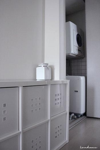 こちらのお部屋では一番奥にランドリースペースがあり、そこに至るまでの廊下に洗濯用品やストック品などを入れておく収納家具を置いていらっしゃいます。シェルフユニットを横置きにしてインボックスを併用し、中身をすべて隠してしまえるタイプの真っ白な収納は、すっきりしていてとてもモダンな印象です。