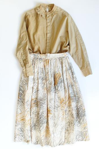 鉛筆で線を描いたようなアーティスティックなスカートは、ベージュのフリルつきボタンダウンシャツで、フェミニンかつノスタルジックに昇華して♪