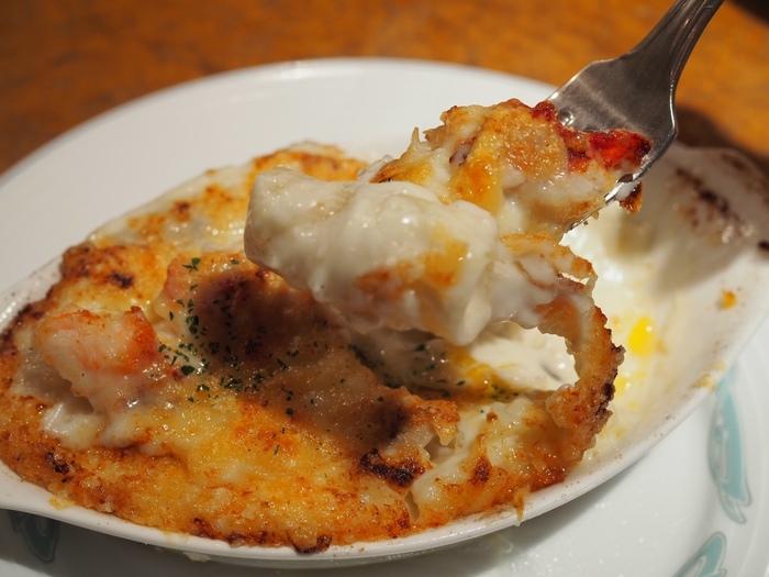 """浅草生まれのオーナー・シェフ、大宮勝雄氏が目指すのは""""平成の洋食""""。ごはんに合う洋食を新しいスタンダードにしたいと日々進化を続けているそう。こちらの「オマール海老のグラタン」は、マカロニグラタンにぷりぷりのオマール海老の切り身がたっぷり入った贅沢なひと皿。しっかりした濃いめのベシャメルソースは、確かにごはんにも合う味です。"""