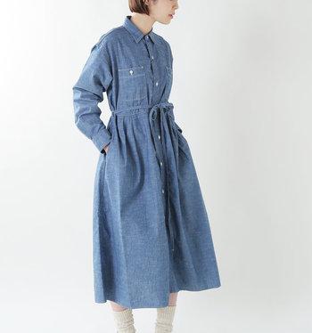 1950年代のヴィンテージワークシャツをイメージしてつくられたドレス。細身の襟やスクエアポケットなどメンズライクなディテールと女性らしいシルエットのバランスが絶妙です。  一枚で着るときは腰紐をキュッと絞ってレディライクに仕上げるのがおすすめ。腰紐の代わりに細めのレザーベルトを使うとより上品に着こなせます。