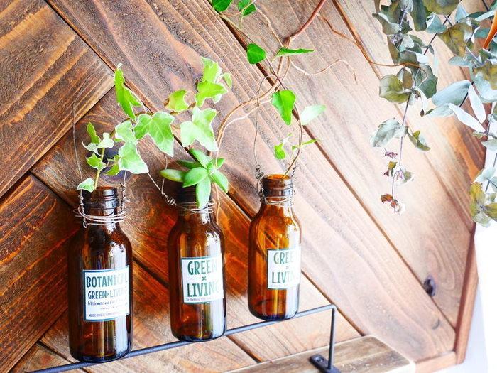 栄養ドリンクの空き瓶に、ワイヤーのハンドルとデザインラベルを貼って花瓶にアレンジ。 グリーンやドライフラワーを飾るのにぴったりです。