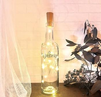 ワインボトルにワイヤーライトを組み合わせたDIY。無数ライトがキラキラとってもきれい。アウトドアなどの照明としても良さそう。