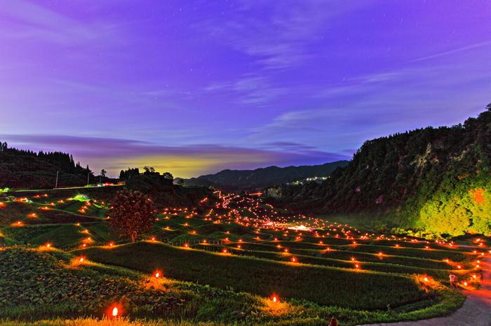 「日本で最も美しい村」連合に加盟している山形県大蔵村の四ヶ村棚田では、「四ヶ村棚田ほたる火コンサート」が開催されます。棚田の畔に燈された灯と棚田が見事に調和し、周囲は幻想的な雰囲気に包まれます。