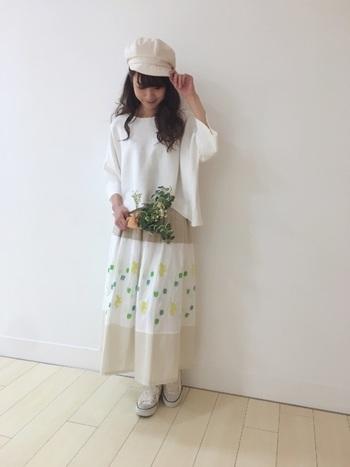 ベージュと白の配色切り替えが、とってもオシャレな印象のロングスカート。白の部分に施された花柄の刺繍は、まるで一枚の絵画のような繊細さを持っていますね。全体を白でまとめたワントーンコーデで、デザイン性の高いスカートをシンプルに着こなしています。