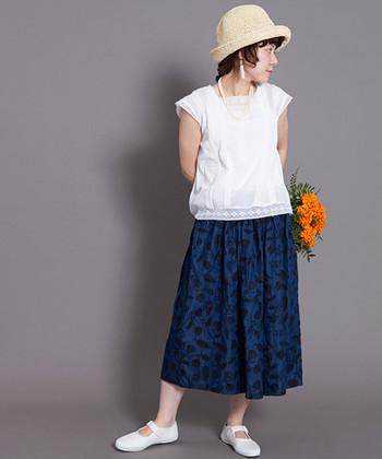 ネイビーのロングスカートに、同系色の糸でさりげなく刺繍を入れた大人テイストな一枚。トップスには白のブラウスを合わせて、春夏らしい爽やかなコーディネートが印象的です。ボトムスが少しダークトーンなので、シューズやハットなので白やベージュなどの明るい色をプラスしています。