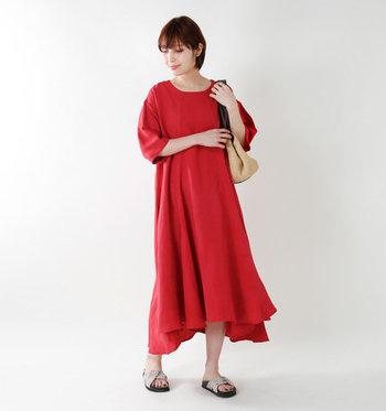 アシンメトリーな裾のドレープが、大人の余裕を感じさせる赤のマキシ丈ワンピース。一枚できてもサマになる計算されたシルエットと、七分袖で春夏を通して着られるデザイン性の高さが魅力的な一枚です。ジャケットやライトアウターを合わせれば、秋コーデにも着回しできそうですよね。