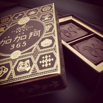 祇園店の看板商品である「加加阿365」。これはその日にしか買うことができない特別なチョコレートなんです。  箱の表にあしらわれているのは、京都の風物詩にちなんだオリジナルの紋。365日分のデザインがあり、その日にちなんだ紋のチョコレートが店頭に並びます。誕生日など訪れる日以外の日付のものが欲しい場合は事前予約ができますよ。  製菓の国際コンクール「WPTC」のチョコレート部門でグランプリを獲得したグランシェフとショコラティエによって作り出された「加加阿365」。  できるだけ火を入れず生ケーキのような味わいにこだわったという五感に響くチョコレート。柔らかい食感に、香り高いカカオとミルク感が味わえ、口どけまで計算し尽くされた渾身の逸品です。