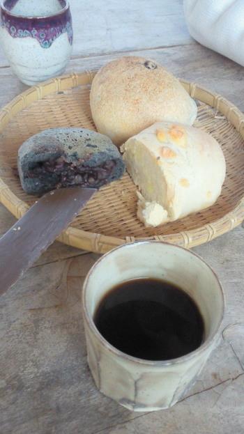 先ほどのデッキで、焼きたてパンをいただくこともできます。左の黒いパンは「竹炭あんパン」。竹炭カンパーニュの生地でオーガニックあんを包んで石窯で焼き上げた全粒粉あんパンです。竹炭パウダーの力でふわふわ・もっちりとした食感が、まるでお餅のようだと人気です。