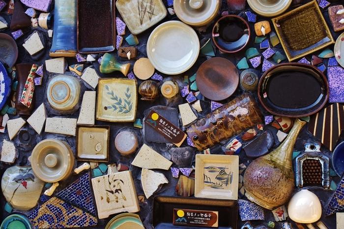 江戸時代末期に、笠間で修行しこの地に窯を開いた大塚啓三郎が始まりと言われる益子焼は、上質な陶土と東京に近い立地によって日用の器の産地として発展しました。「用の美」を追求した民芸運動家の1人・濱田庄司が1924年に移住し影響を与え「芸術品」としての評価も加わりました。 こちらは、トイレの壁です。ランダムにコラージュされた益子焼の器が美しいですね。