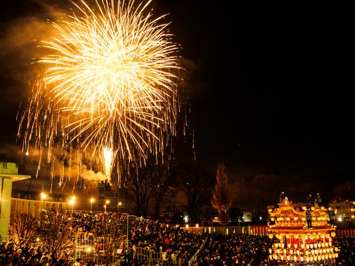 羊山から打ち上げられる花火が冬の澄んだ夜空を鮮やかに彩り、祭りは熱気に包まれます。