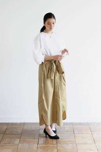 シャツワンピースをマキシ丈のスカートにとしてはくと、まるで全く違うアイテムのよう! ウエストまでシャツのボタンを外して、リボンベルトのように袖を結んでいます。