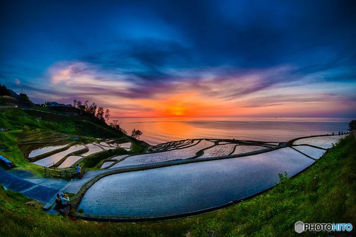 夕暮れ時になると、白米千枚田では傑出した美しい風景を見せてくれます。沈みゆく夕陽、夕陽によって赤く染まった海と雲、水鏡のような水田が織りなす景色は、絶景そのものです。