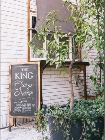 代官山駅から徒歩5分の「King George(キングジョージ )」。ホワイトカラーのウッディーな外観が目印のこちらは、実は美味しいサンドイッチを食べる事ができるバータイプのお店。