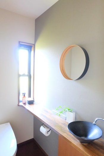 陶器の洗面台や木製のナチュラルな棚板のあるちょっぴりモダンなトイレには、丸い鏡がぴったり。やわらかい印象になります。