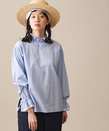 2枚仕立てのフリルが目を引くスタンドカラーのシャツ。袖のデザインもディティールが凝っていて洗練されています。サックスカラーのストライプがとても爽やかですね。