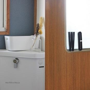 レトロな建具にマッチするブルーグレーのアクセントクロスが張られたトイレの壁。落ち着いた雰囲気で素敵です。