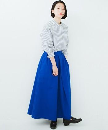 こちらは鮮やかなブルーのスカートと、上品な配色のストライプシャツを組み合わせた爽やかなコーディネート。クラシカルなローファーが足元を可愛く見せてくれます。シャツ×スカートの定番スタイルも、旬のスタンドカラーを取り入れることで新鮮な印象になりますね。