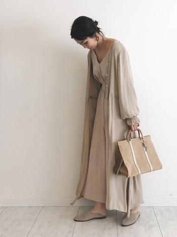 洋服も小物も、オールライトベージュでまとめたワントーンコーデ。ロングワンピースにロングガウンを重ねたレイヤードスタイルも、ふんわりと柔らかな雰囲気に。自然素材やバブーシュサンダルで大人ナチュラルな印象のスタイリングです。