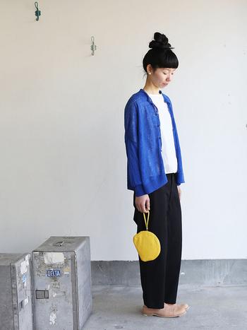 ブルーのシャツを着流し、手元にはイエローのミニバッグを。深いブラックのパンツが、それぞれの色をはっきりと引き立てます。