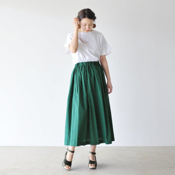 一見シンプルな白トップスのように見えますが、花びらのように重なったペタルスリーブが繊細な印象を与えるカットソー。鮮やかなグリーンのロングスカートにトップスインして、女性らしい爽やかコーデの完成です。