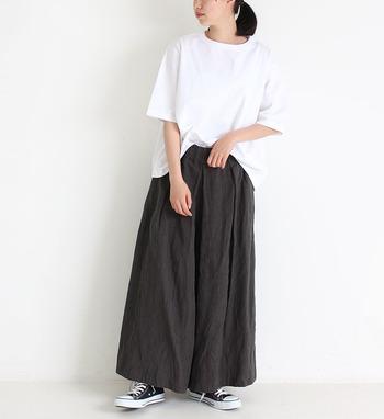 シンプルな白のTシャツを、黒のロングスカートにフロントインしたスタイリング。スニーカーも定番のシンプルアイテムをチョイスして、プレーンを極めた大人のゆとりを感じさせるコーディネートの完成です。